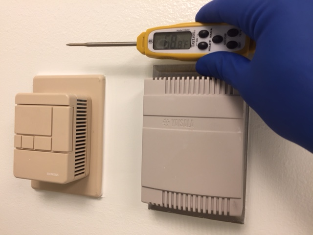 Picture of a person checking wall thermostats with a temperature gauge